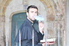 Handsome young priest smoking close up.  Royalty Free Stock Photography