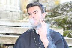 Handsome young priest smoking and looking away.  Royalty Free Stock Image