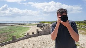 Handsome young professional photographer taking photos outdoor beach coast seaside royalty free stock photography