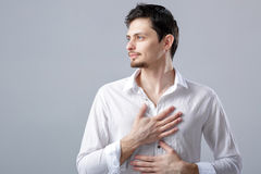 Handsome young proud man in shirt holding hand on chest on grey Stock Image