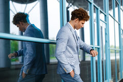 Handsome young redhaired businessman looking on watch Stock Photography