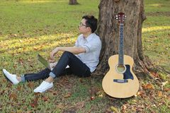 Handsome young relaxed man sitting on green grass and happiness with laptop against acoustic guitar in the park outdoors Royalty Free Stock Images