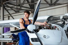 Handsome young repair man fixing plane engine Royalty Free Stock Image
