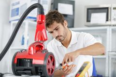 Handsome young repairman fixing vacuum cleaner stock photography