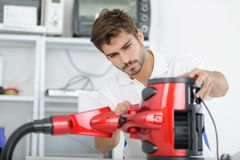 Handsome young repairman fixing vacuum cleaner royalty free stock photography