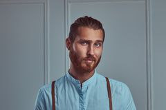 Handsome young retro stylish redhead man in suspenders posing against a white wall in a studio. royalty free stock photography