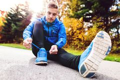 Handsome young runner sitting, tying shoelaces. Stock Images