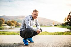 Handsome young runner squatting down. Royalty Free Stock Photo
