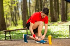 Handsome young runner tying shoelaces on the track in the spring park. Near him is an orange thermocouple royalty free stock image