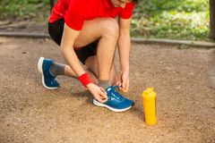 Handsome young runner tying shoelaces on the track in the spring park. Near him is an orange thermocouple royalty free stock images