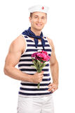 Handsome young sailor holding a bouquet of flowers Stock Photo