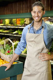 Handsome young sales clerk standing near stall in supermarket Stock Photography