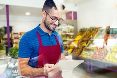 Handsome young salesman using his digital tablet in health grocery shop. Shot of handsome young salesman using his digital tablet in health grocery shop royalty free stock photography