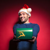 Handsome young santa giving you a green gift Royalty Free Stock Images