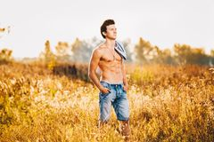 A handsome young man with a strong muscular torso in an unbuttoned shirt is standing on a meadow in nature outside city. A handsome young man with a strong