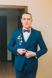 Handsome young short hair athletic man dressed in blue suit posing indoor fixing buttons on his blazer Royalty Free Stock Image