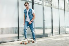 Handsome young skater in denim clothes. Riding skateboard stock photo