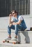 Handsome young skater sitting on stairs with skateboard. Looking away royalty free stock photo