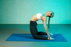 Handsome young slim gymnast woman in sports clothing stretching on brick wall in neon lights. Flexible muscular woman stock images