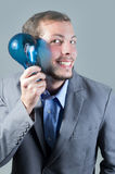 Handsome young smart man holding a blue light bulb Royalty Free Stock Photos