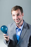 Handsome young smart man holding a blue light bulb Royalty Free Stock Images