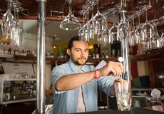 Handsome young smiling bartender holding steel swizzle spoon in. Handsome young smiling bartender behind the bar counter holding steel swizzle spoon in the glass Stock Photography