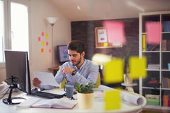 Handsome young smiling businessman working with documents. In office stock photos