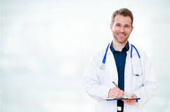 Handsome young smiling doctor with clipboard Royalty Free Stock Photos