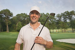 Handsome young smiling golfer holds club on a course Royalty Free Stock Photos