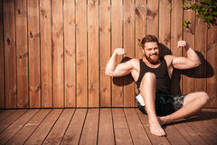 Handsome young smiling man sitting and showing muscles. Over wooden background Stock Photos