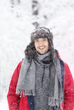 Handsome young smiling man in winter forest. snowing day. Handsome young smiling man in winter forest with hat, scarf and red jacket. Winter fashion Stock Photo