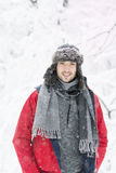 Handsome young smiling man in winter forest.snowing day. Handsome young smiling man in winter forest with hat,scarf and red jacket.Winter fashion Royalty Free Stock Images