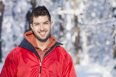 Handsome young smiling man in winter forest.snowing day. Handsome young smiling man in winter forest with hat,scarf and red jacket.Winter fashion Stock Images