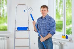 Handsome young smiling painter holding paintroller looking at ca. Mera Royalty Free Stock Photo