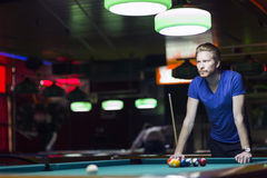 Handsome young snooker player bending over the table Stock Images