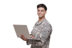 Handsome young soldier with a laptop Royalty Free Stock Photos