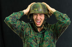 Handsome young soldier wearing uniform suffering from stress with his hands touching his helmet and screaming, in a. Black background stock photo