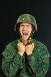 Handsome young soldier wearing uniform suffering from stress, screaming with both hands doing fist, in a black. Background stock photo