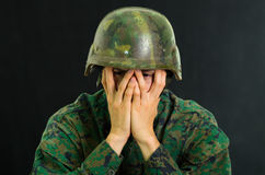 Handsome young soldier wearing uniform suffering from stress, using both hands to cover his face, in a black background.  stock photo