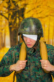 Handsome young soldier wearing uniform suffering from stress, with a white bandage around his head and covering his eye. With a backpack in a burred yellow stock image