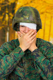 Handsome young soldier wearing uniform suffering from stress, with a white bandage around his head and covering his eye. With both covering his mouth, in a stock photography