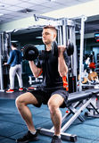 Handsome young sportive male in sportswear lifting some weights. And working on his biceps in a gym Stock Photos