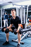 Handsome young sportive man in sportswear lifting some weights. And working on his biceps in a gym Royalty Free Stock Photo