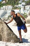 Handsome young sports man stretching work out at the beach Stock Image