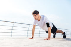 Handsome young sportsman doing plank exercise at the pier outdoors Stock Photography