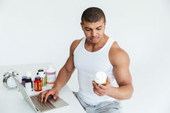 Handsome young sportsman holding sport nutrition and using laptop computer Stock Photos