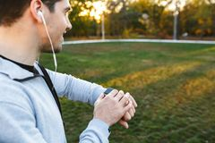Handsome young sportsman outdoors in park listening music with earphones looking at watch royalty free stock images