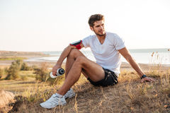 Handsome young sportsman sitting and holding bottle of water outdoors Royalty Free Stock Photos