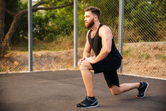 Handsome young sportsman stretching legs during workout outdoors. Handsome young bearded sportsman stretching legs during workout outdoors Stock Image