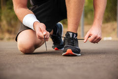 Handsome young sportsman tying shoelaces on his sneakers Royalty Free Stock Images